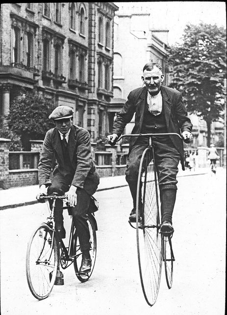 Two gentlemen riding bicycles, one a standard, the other a penny farthing. By Beamish Museum.