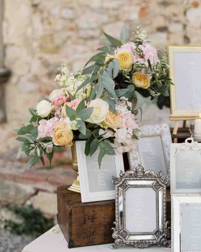 The table assignments were displayed in various vintage-style picture frames. Gold vases containing roses, hydrangea, and stock flower decorated the setup.