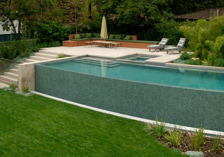 Pool wall is fence. Gate at base of steps. Plants surrounding pool protecting it. Built-in seating