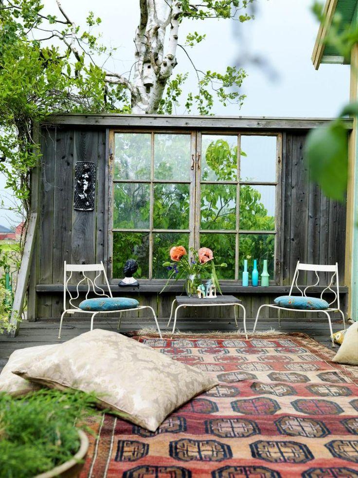 LEVEGG: Denne uteplassen har fått en vegg med gamle vinduer ut mot en åker. Teppet og gulvputene gir en følelse av utestue. Møblene har beboeren Palle Rolfsson sveiset sammen selv. Teppe, vaser og figuerer er kjøpt på loppemarked.