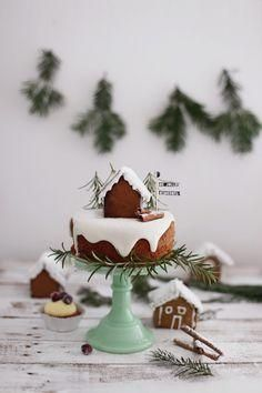 Adorable gingerbread cake topped with royal icing snow, a snowy homemade DIY gingerbread house and a rosemary mini Christmas pine tree forest. So adorable, festive, and a delicious holiday dessert. Also a fun Christmas gift DIY to make with kids!