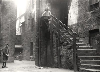 """A young woman at a communal sink in a backcourt at 50 Crown Street, Gorbals, c 1925. The door behind her appears to be that of the toilet. Outside toilets were a common feature of Glasgow tenements until the late 19th century. Subsequently tenements were built with or renovated to include a shared water closet on each stair landing. Refuse can be seen piled up in the """"midgie"""" (midden) at the back of the courtyard."""