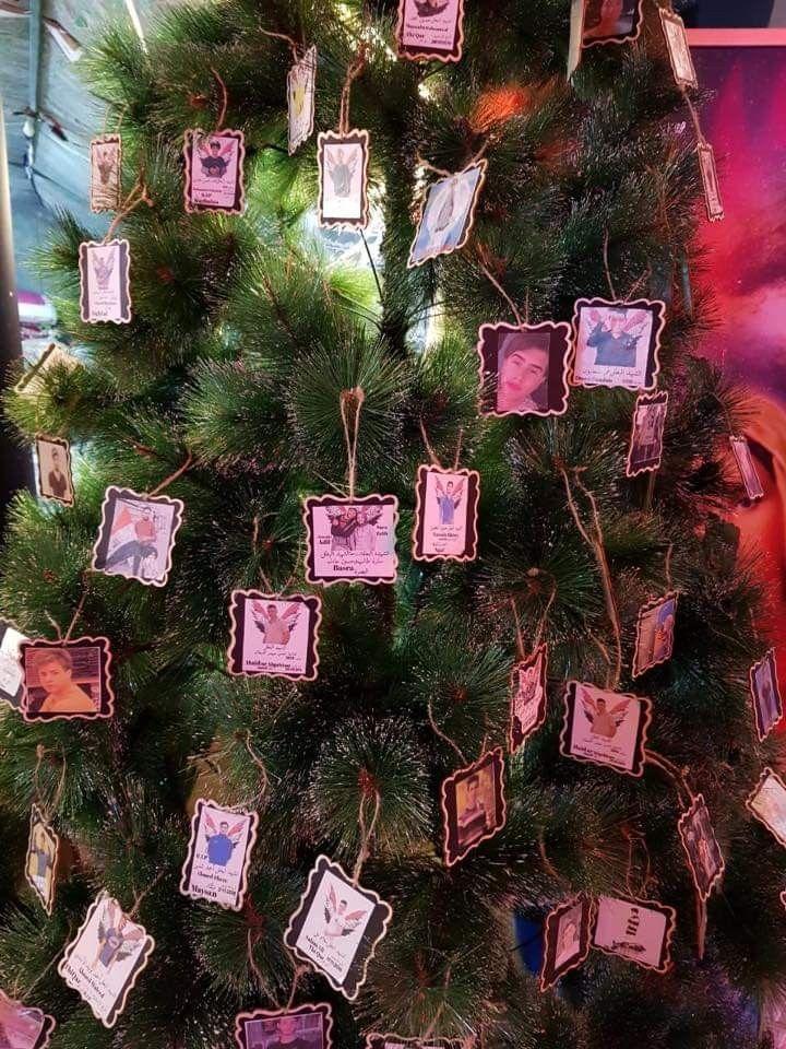 شجرة عيد الميلاد الكريسماس في التحرير تتزين بصور الشهداء حاطين تماثيل العذراء ويسوع و صور الشهداء و شموع و مشغلين قصيدة حسينية هذولة الشباب عدهم وعي و تعايش