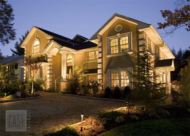 Landscape lighting design featuring elegant uplighting and path lighting using cast lighting fixtures