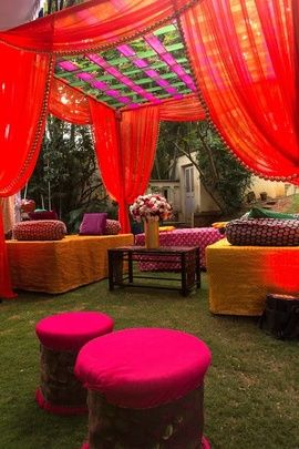 Mehendi Decor - Hot Pink and Orange Color Decor | WedMeGood Beautiful outdoor mehendi decor, with pink round cushion seatings, orange and green curtain tents and floral table arrangements. #wedmegood #decor #mehendi #wmgdecor #pink #orange