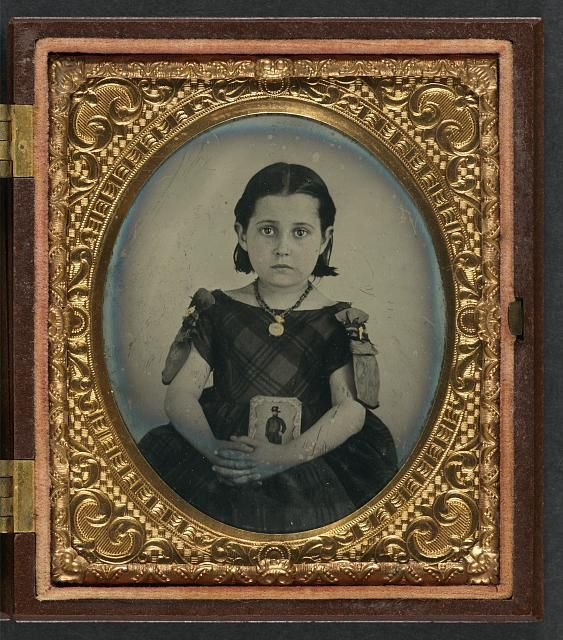 [Unidentified girl in mourning dress holding framed photograph of her father as a Civil War cavalryman with sword and Hardee hat]