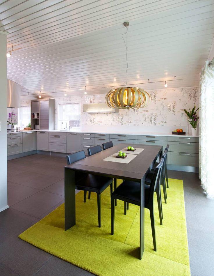 FARGEKLATT: Fargen på kjøkkenfronten er i en dus gråbrun tone, som skaper varme mot det hvite. Et limegrønt gulvteppe komplementerer taklampen. Kjøkkenet er stort, med mye benkplass og åpent gulv. Eierne har derfor valgt å kombinere spisestue og kjøkken.