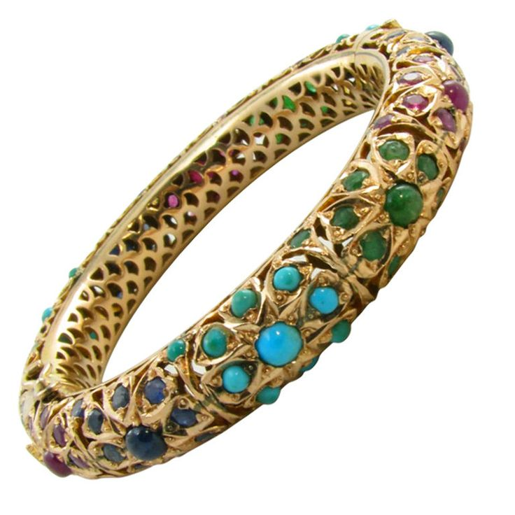An Indian 9 carat rose gold, sapphire, turquoise, emerald and sapphire bangle bracelet. Circa 1960's. The bangle is set with numerous alternating stone set sections in an openwork pierced gold design. The bangle weighs approximately 53.1 grams and has an interior diameter of 2 3/16 inches.
