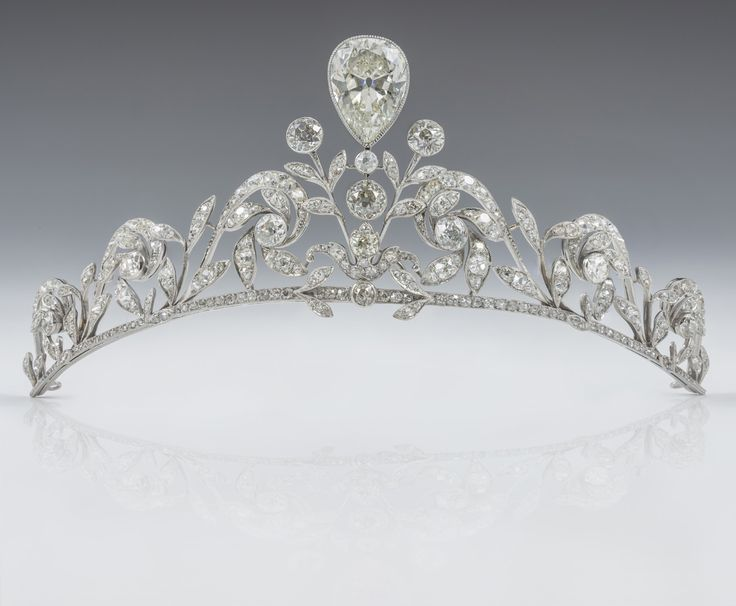 The Belgian Lannoy family tiara composed of 270 old-cut brilliants set in platinum, with a diamond in an inverted pear shape in the centre. A dozen larger brilliants stand out owing to their closed sets, appearing like buttons along the patterns of leafed scrolls. The tiara was made by Altenloh in Brussels. Ernest Altenloh, son of a silversmith, created the company in 1878.