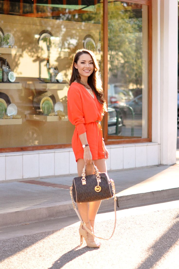 Shop this look on Lookastic: https://lookastic.com/women/looks/orange-playsuit-beige-leather-heeled-sandals-dark-brown-leather-duffle-bag/14709 — Orange Playsuit — Dark Brown Leather Duffle Bag — Beige Leather Heeled Sandals