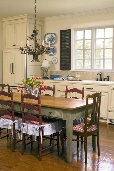 "Whitewashed cabinetry and expansive windows create a light and inviting kitchen. ""Eclectic French Country."""