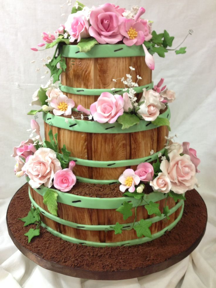 Flower Barrels with roses - 3 tiered wedding cake is all strawberry and vanilla marbled cakes, with bc icing, covered in fondant with hand painted, fondant boards and trim, chocolate cookie dirt and gumpaste ivy and flowers.