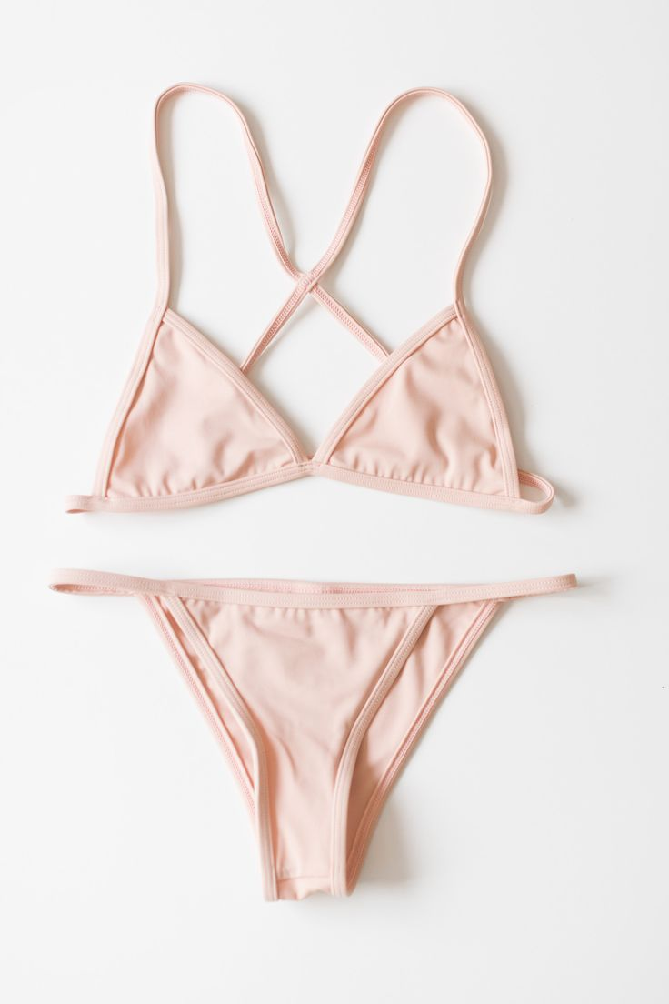 Simple and minimal triangle bikini top with a cross back and cheeky string side bottoms. Fully lined. Comes in blush pink or white. - 80% Nylon 20% Spandex - Made in USA