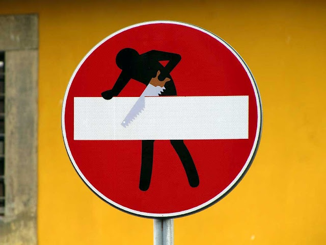A guy with a handsaw at work on the bar of a no entry sign.