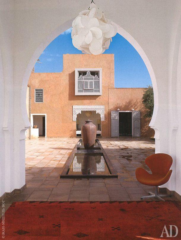 В центре дома находится патио с фонтаном. На переднем плане — берберский ковер и кресло Swan по дизайну Арне Якобсена.