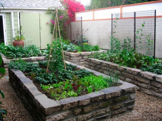 Broken concrete can be obtained for free. Stacked, it makes a great foundation for a raised bed. Mortaring is optional.