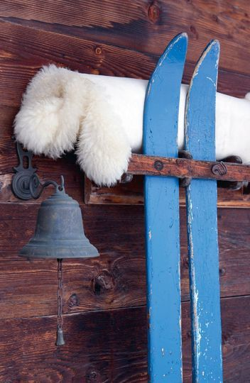 Outdoor decor made with fur, blue skis and a ring bell for this chalet