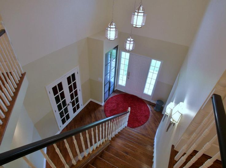 This entry way and staircase was remodeled by 7J Design.  The final touch?  A red rug.