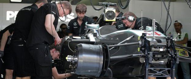 Mercedes mechanics fix British driver Lewis Hamilton's car at the team's garage after its engine failure during the first practice session
