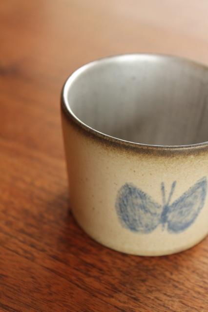「三谷カップ」と名付けられた安藤さん作の陶器のカップ。  そこへ皆川さんが、ちょうちょを絵付け。