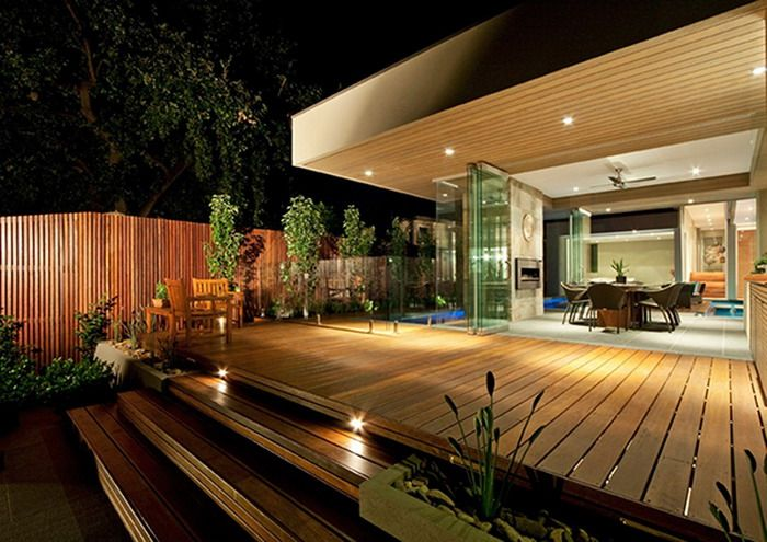 Modern garden doors from the house leading onto the decked area with a table and chairs and steps leading to the grass area. Nice lights on the decking steps. A nice hidden surprise around the corner a swimming pool.  #decking #gardendecking #patio #swimmingpool #garden #inspiration #gardenlighting  Image source: www.decoragogo.com