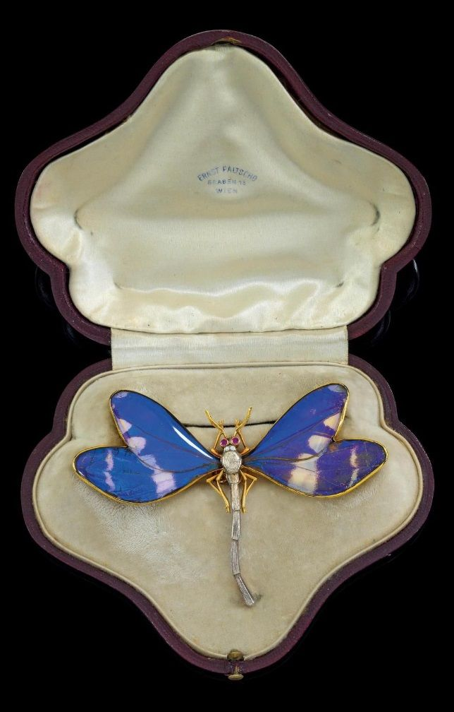 An Art Nouveau gold, silver, diamond and gem set brooch, by Ernst Paltscho. Designed as a dragonfly with blue and white enamelled wings or real butterfly wings, the body set with diamonds and with rubies as eyes, mounted in silver and gold. Bearing an assay mark for 1872-1922 and patent registration mark. #Paltscho #ArtNouveau #brooch