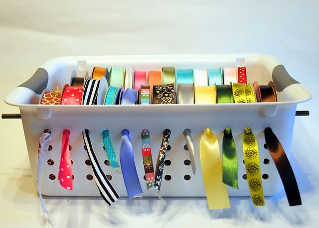 Easy, cheap ribbon organizer - narrow wooden dowels and a holey plastic basket.