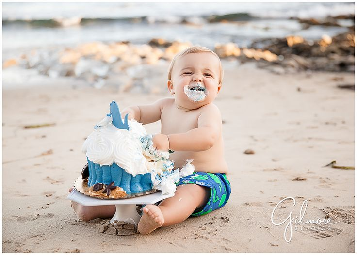 Baby Boy Beach Cake Smash-Orange County Newport Beach, Babies, Toddlers, Children, kids, Baby Outfits, what to wear, shades of blue, colored eyes, cute babies, giant cupcake, cakes, cake smash, great dane bakery, seashells, waves, rocks, whale, baby board shorts, smiling and laughing baby, chubby cute, adorable, family cake smash, husband and wife team photographers, Orange county, the beach, GilmoreStudios.com