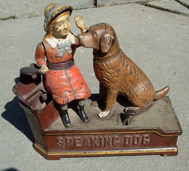 Mechanical cast iron bank. The coin is placed on a plate held by the girl and when the lever is pushed she drops the coin into a trap door (which has its top missing) and the dogs mouth opens and her hand moves along with the dogs tail.