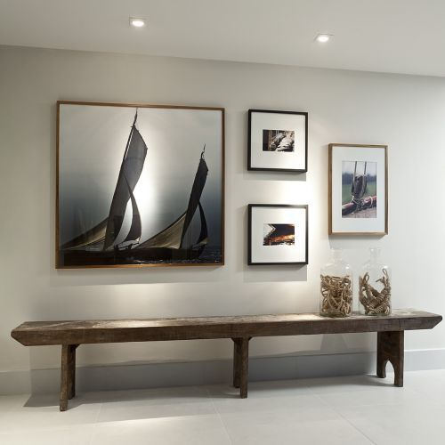 Entrance Hall - Framed photo gallery with one long natural wood bench. Simplistic & beautiful.