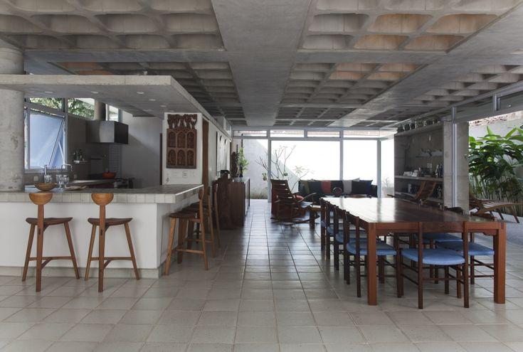 Ambientes integrados e laje em concreto e estrutura aparentes.