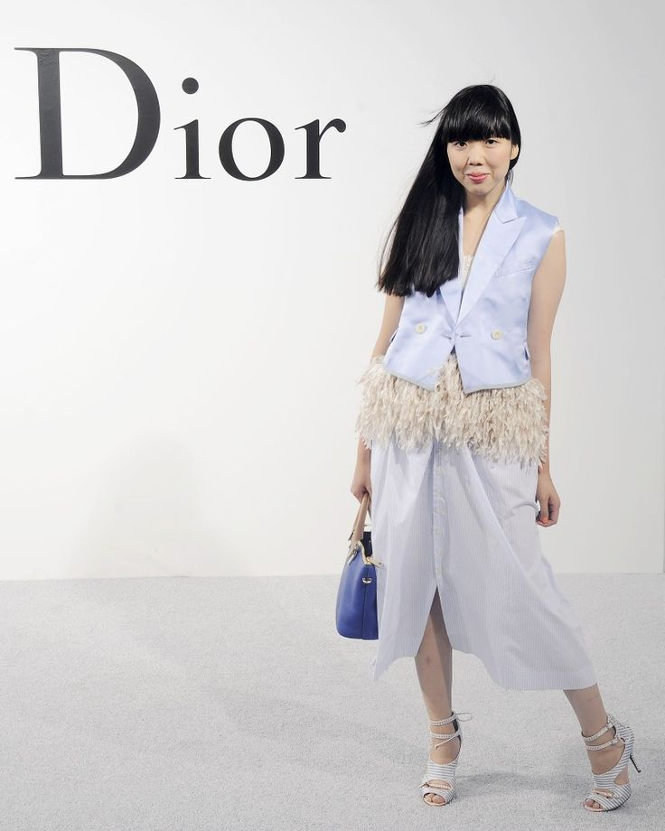 Susie Bubble wearing Wearing Sacai satin waistcoat and fringed zipper top, vintage Calvin Klein skirt, Tabitha Simmons shoes, Chloe bag/Photograph from Rex Features at Dior Cruise 2015