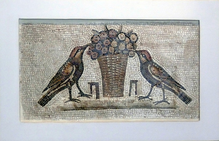 A large basket, decorated with olive tree leaves, full of big olives, is on the ground. Two trushes, on each side of the basket, are picking at the fruit.  Roman era, Sousse, Archeological Museum of Sousse