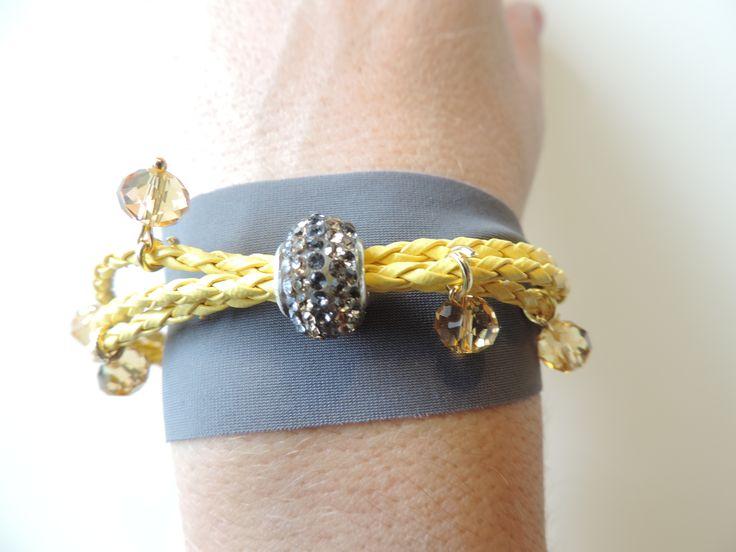 Bracciale in eco-pelle intrecciata di colore giallo e fettuccia grigia, con charm grigio e champagne, pendenti con cristalli di colore giallo paglierino. Chiusura dorata con moschettone.