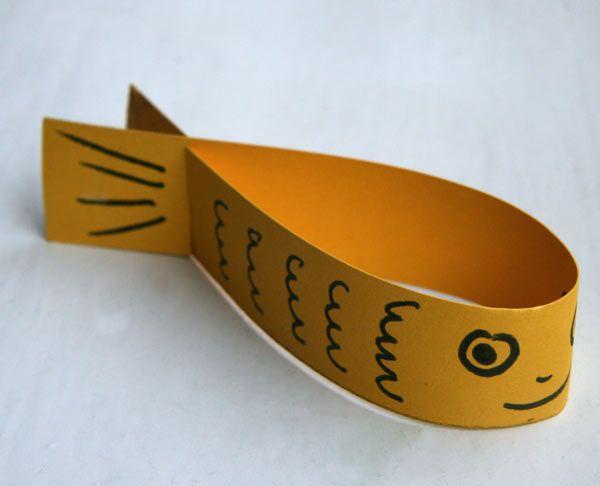 Poisson volant: Loris colorie une bande de papier. tu dessines le visage du poisson. Tu fais 2 entailles au bout (une dans chaque sens). Tu assembles. Quand tu lances en l'air le poisson, il redescends en tourbillonnant !!