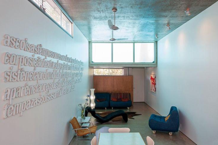 A decoração da Slice House mistura peças de design assinadas pelos arquitetos do escritório britânico Procter-Rihl, também responsáveis pela arquitetura, com outras da coleção da proprietária da residência. Há um choque de cores - berinjela x verde abacate, azul x laranja e tons de vermelho - e o poema, de Arnaldo Antunes, preenche a grande parede à esquerda