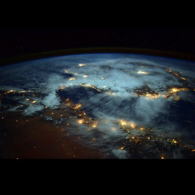 """""""Spiral of lights BURSTING from Earth!  #Spain looks like it is floating away from #Africa"""" #AstroButch  Photo Credit Barry Wilmore: 123F5312a  #nasa #nasajsc #spacestation #internationalspacestation #explore #exploration #photography #ISS #Exp42 #cupola #geography #EarthArt #art #clouds #overcast #night #Arora #atmosphere  #Mediterranean"""