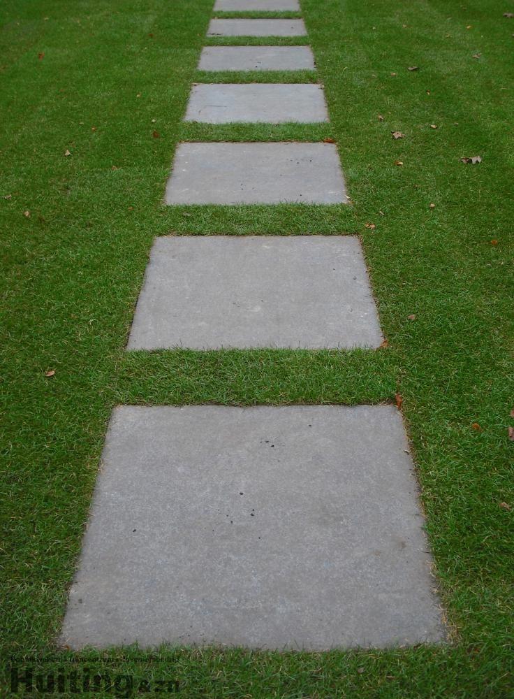 Gras met grote tegels om een pad naar de poort achter in onze tuin te maken