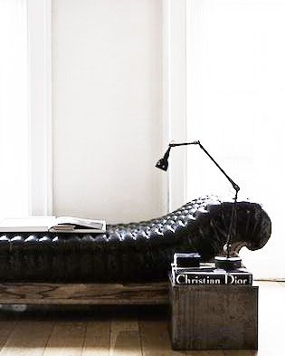 low couch or bed against floor length windows. reading lamp. wood.