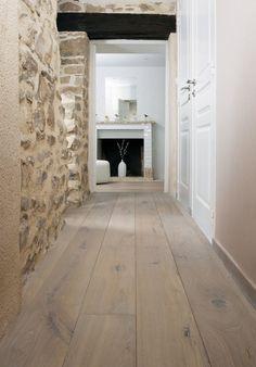 <p>Parce qu'il est recouvert de larges lames de parquet contrecollé en chêne blanchi, huilé Authentics, ce couloir joue sur les matières et les contrastes de la pierre au...