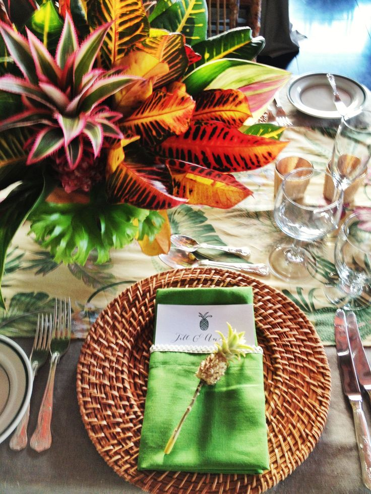 Centerpieces of tropical foliage in fun colors. We could alternate the tables with arrangements done in this style, and mix it in with something more floral. I think it would look really chic!