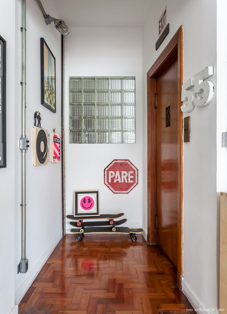 Hall de entrada com quadros e tubulação de iluminação aparente.