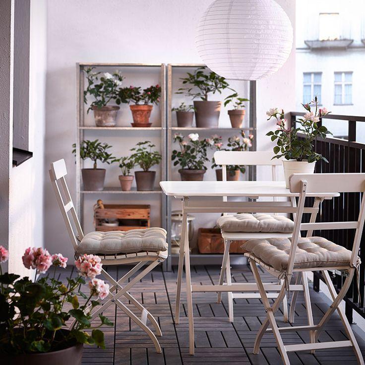 Balkong med vita klappstolar och fällbart bord samt hyllor i förzinkat stål
