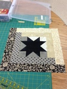 I like the black and white log cabin in the background of this square.  Could be cool to use a color for the Ohio Star in the center.  Same color throughout entire quilt or different.