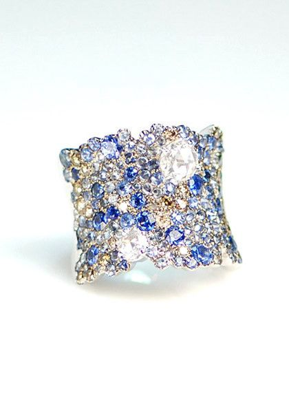 """A wonderfully dramatic and generously sized (nearly 1"""" wide) ring by Stefan Hafner. This """"Lunar"""" ring showcases 4.63ctw of white diamonds and 1.45ctw sapphires set in 18k white gold. The variagated st"""
