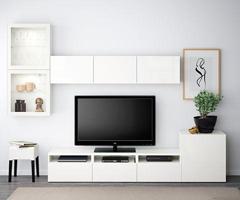 BESTÅ tv- og medieopbevaring med hvide låger og vitrinelåger, en hvid bordlampe, et blåt, rundt tæppe og en grøn væg