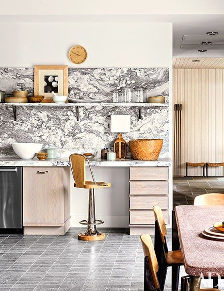 A Laura Resen photograph is propped next to the kitchen's wall clock, both from Aero | archdigest.com