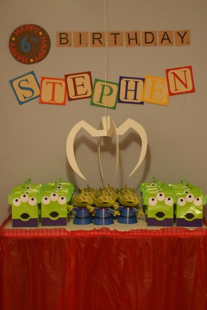 Cute idea for Toy Story Party - Hang a 'claw' above the Alien hats & favor bags