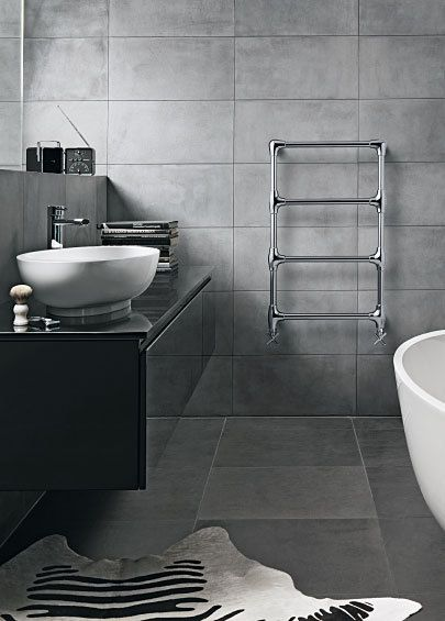 This grey bathroom has a masculine element - large block tiles and ladder style rail
