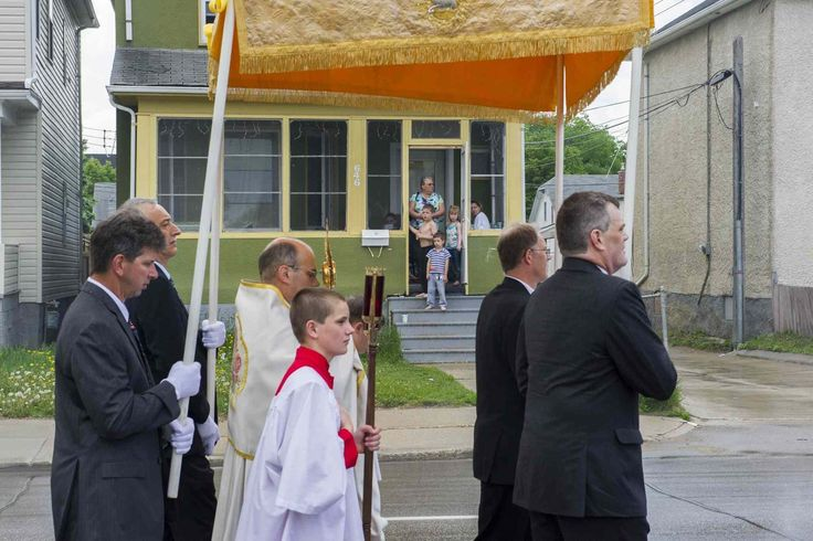 A family watches a Traditional Solemn Procession go by on Mountain Avenue Sunday morning. About 100 people participated in the celebration of the feast of Corpus Christi with a Traditional Solemn Procession starting at Our Lady of the Rosary Roman Catholic Church Sunday.